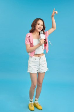 Young happy and beautiful Asian girl singing karaoke song excited, cheerful emulating pop music star