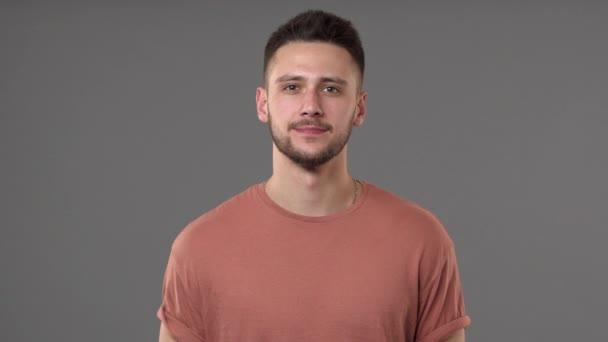 Portrét closeup Evropské mladíka nosí ležérní tričko na tebe dívá a usmívá se, izolovaných nad šedým pozadím studio zpomalené. Pojetí emocí