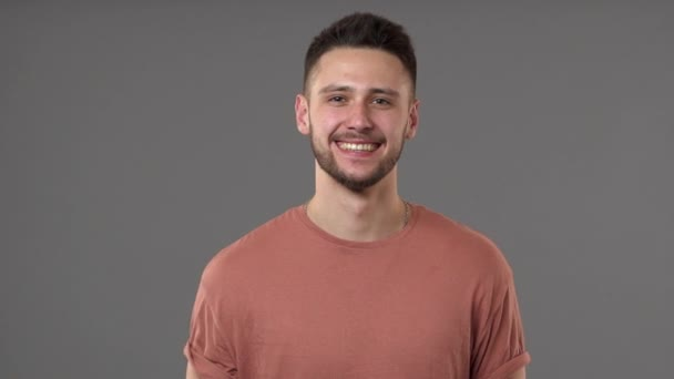 Portrait closeup of brunette positive man wearing casual t-shirt chuckling and grinning with perfect smile, isolated over gray background in studio slow motion. Concept of emotions