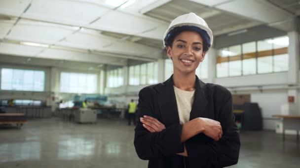 Portrét úspěšné afroamerické ženy v helmě a oblek stál s rukama přešel do velké světlé místnosti výroby zpomalené
