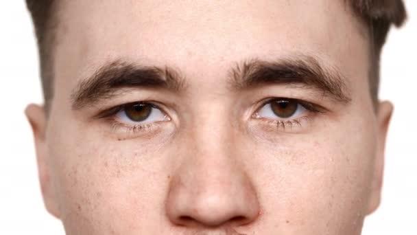 Makro pohled pohledný muž s oříškově hnědé oči při pohledu na fotoaparát s laskavý pohled a úsměv, izolované na bílém pozadí v detailním studio. Pojetí emocí