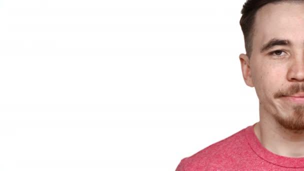 Polovina strany portrét pohledný muž 30s s vousy a knír s úsměvem poblíž copyspace, izolované na bílém pozadí v detailním studio při pohledu na fotoaparát. Pojetí emocí