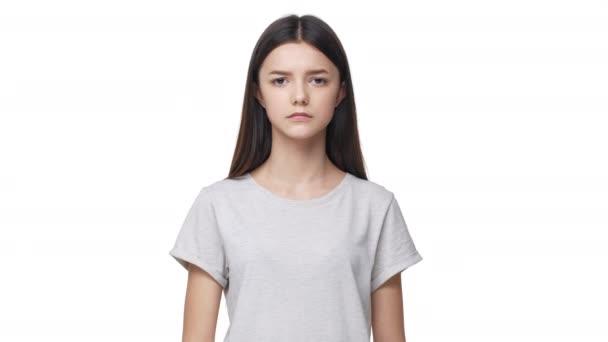 Portrét vážné brunetka školačka s dlouhými vlasy dělá Ššš gesto s ukazováček na rty a chce zachovat mlčení nebo Nerušit, izolované na bílém pozadí. Pojetí emocí