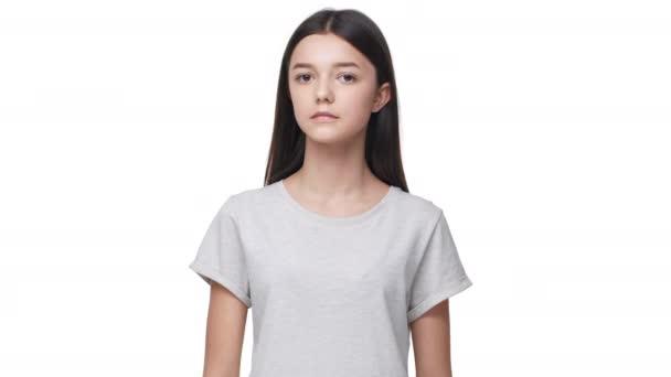 Rövíd szörű kaukázusi nő, hosszú, sötét haj, alapvető t-shirt látszó-on fényképezőgép-szép mosollyal, elszigetelt, felett fehér háttér stúdióban portré. Az érzelmek fogalma