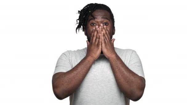 Portrét emocionální afroamerické muže s afro účes vyjádření překvapení a pokrývající otevřená ústa rukama izolované na bílém pozadí. Pojetí emocí