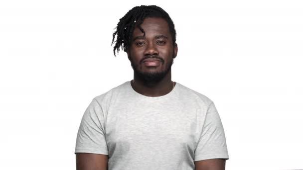 Afro frizurával alkalmi póló köszöntés kézzel integetett a fényképezőgép-val mosolyog, elszigetelt fehér háttér felett a nagy afrikai amerikai férfi portréja. Az érzelmek fogalma