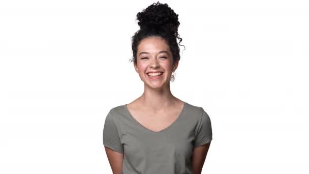 Portrét pozitivní kudrnaté ženy 20s na sobě základní tričko, směje se na vás a vyjádření radosti, izolované nad bílým pozadím. Pojetí emocí