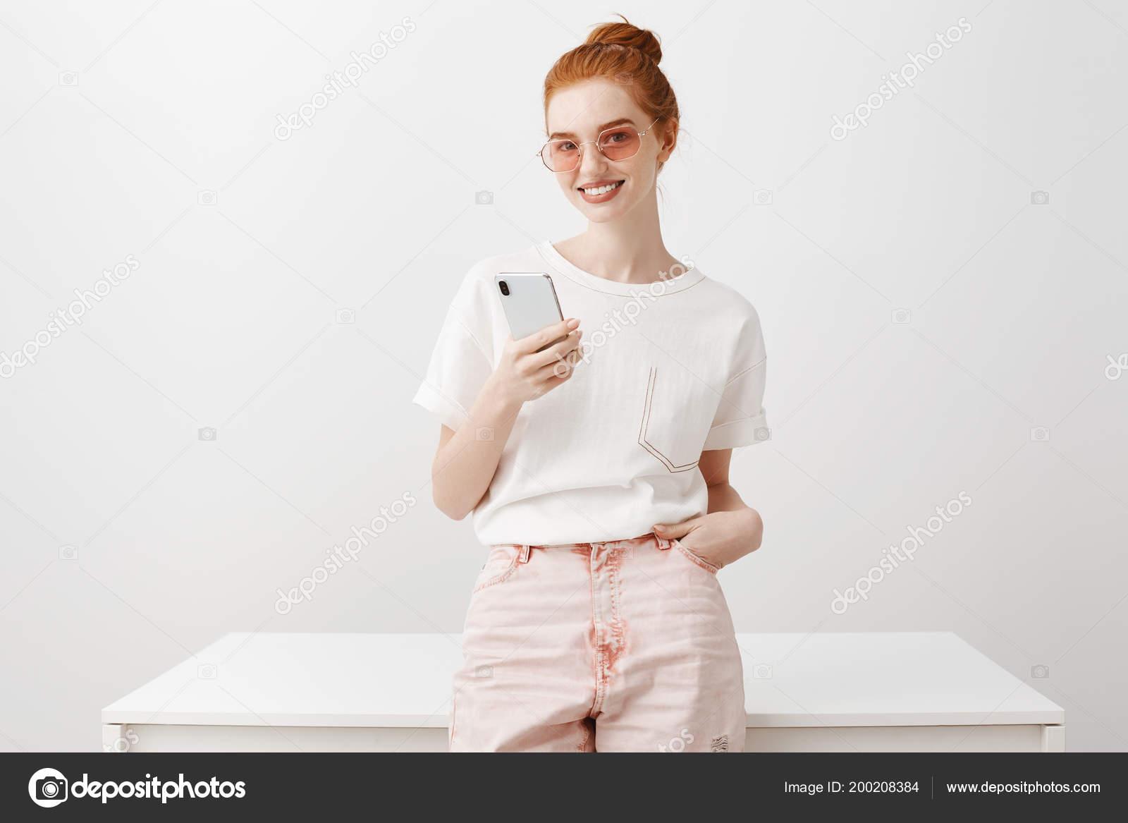 cad255a9c Retrato de mulher ruiva atraente em óculos de sol da moda, segurando o  telefone e apoiando-se na mesa ao mesmo tempo com alegria a ...