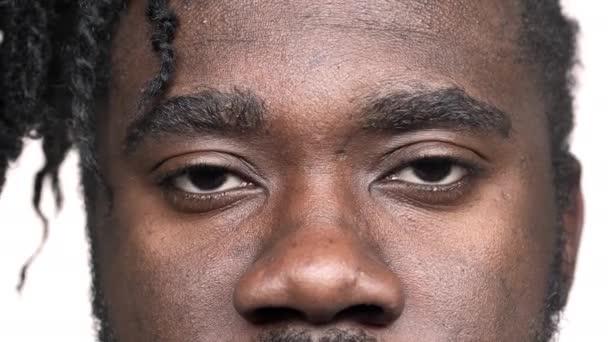 Makro pohled hezký dark pletí muž s afro copánky s laskavý pohled při pohledu na fotoaparát a úsměv, izolované na bílém pozadí v detailním studio. Pojetí emocí