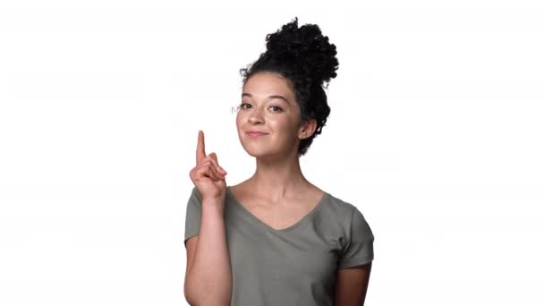 Portrét svůdné ženy 20s v ležérní tričko s vlasy v žemli směřují prst na fotoaparátu což znamená Hej, izolované nad bílým pozadím. Pojetí emocí