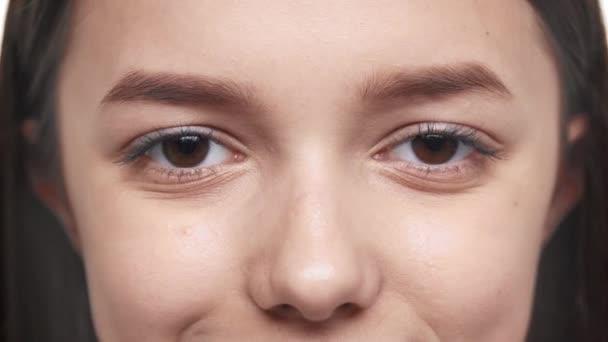 Extrémní closeup portrét dospívající ženy šťastné 20s s čistou pokožku při pohledu přímo a usmívá se makro pohled ženské oříškově hnědé oči