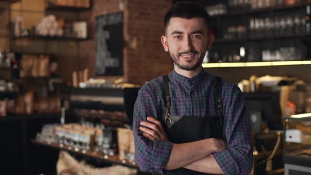 Portrait of caucasian barista guy wearing apron smiling and standing with arms crossed, inside bar or coffee house
