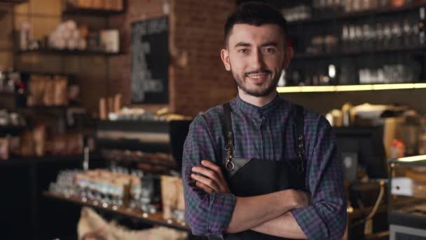 Porträt des kaukasischen Barista Kerl trägt Schürze lächelnd und Stand mit Arme gekreuzt, in bar oder einen Kaffee Haus