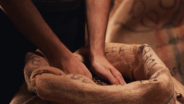 Detailansicht in Zeitlupe von männlichen Händen greifen gebratenen gekochten Robusta oder Arabica-Kaffeebohnen aus Sack und Kontrolle der Qualität des Produkts