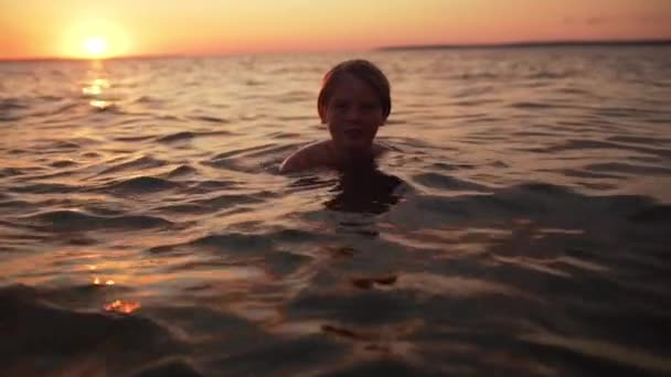 Portrait of young caucasian boy 10-12 swimming in sea alone and looking at you, during amazing dusk in slow motion