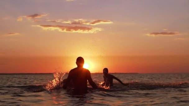 Siluette del padre con due figli di 10-12 nuotare nel mare e spruzzi dacqua insieme, durante il bellissimo tramonto al rallentatore
