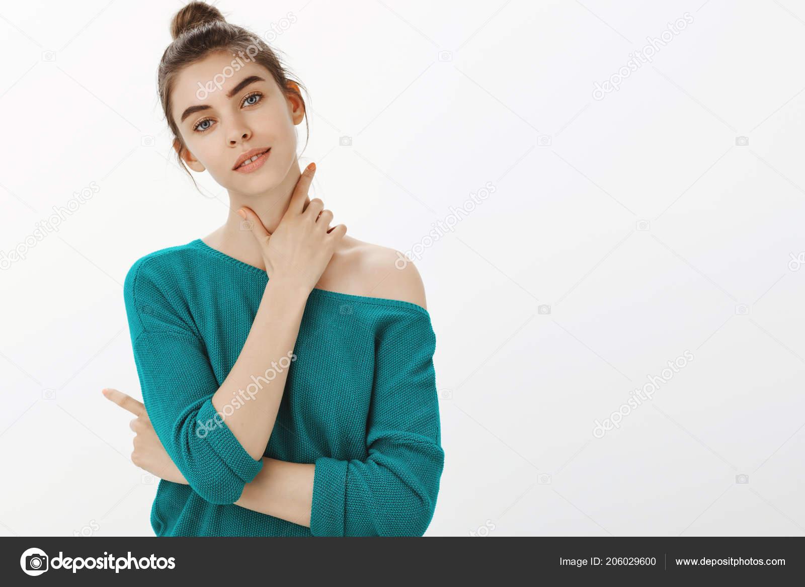 728df78bc Estúdio de tiro de concurso feminina mulher Europeia na camisola solta,  suavemente tocando o pescoço e segurando o braço atravessado enquanto  inclinando a ...