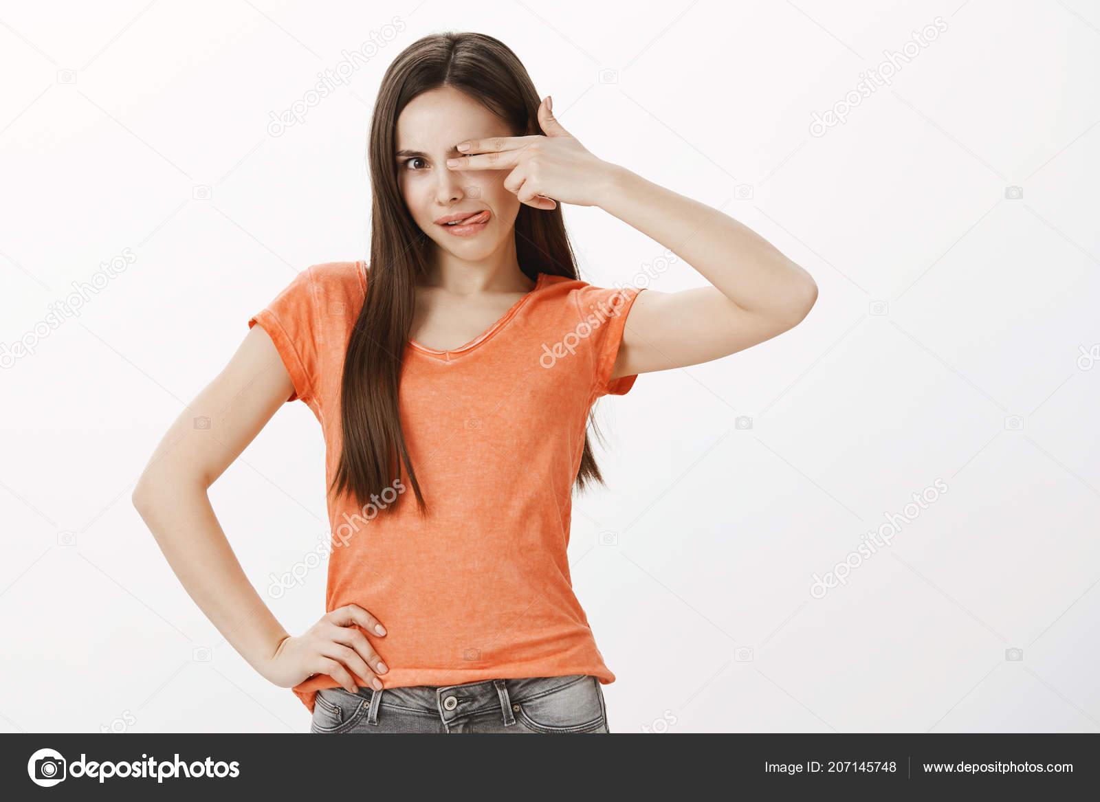 5cf51bc12 Tiro de estúdio de despreocupada infantil Europeu Feminino estudante com  atitude positiva, cobrindo o olho com gesto de arma de dedo, mostrando  língua ...