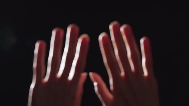 Ritratto della siluetta di due offuscata closeup indoeuropeo mani femminili sollevato verso lalto contro shining, isolato sopra priorità bassa nera