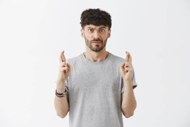 Man praying wife would not know about his mistake. Intense worried and nervous good-looking funny urban male with beard raising one eyebrow pursing lips and crossing fingers for good luck or wishing