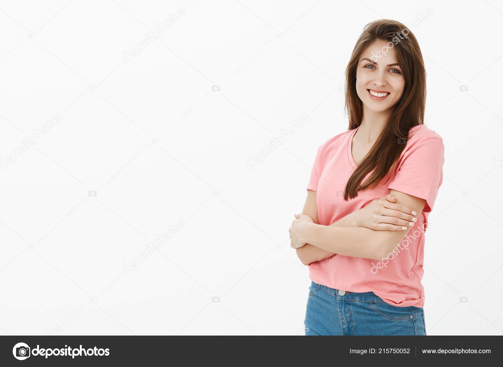 e272c29a077c Positive entspannte süße Kaukasische Mädchen mit braunen Haaren, Hand in  Hand auf Brust gekreuzt und grinsend in die Kamera, Gefühl schüchtern beim  Versuch ...