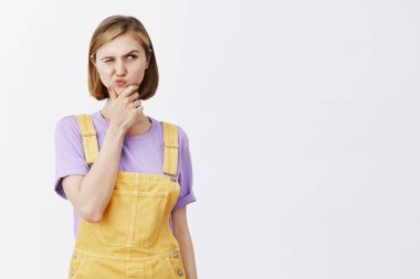 Hmm, what if. Portrait of intrigued doubtful smart urban female in stylish yellow dungarees, lifting eyebrow in curious expression, rubbing chin and gazing aside while thinking, making assumptions