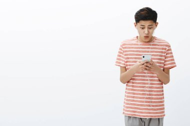 Impressed happy excited attractive young asian male with cool hairstyle in striped t-shirt holding smartphone looking pleased and amazed at cellphone screen saying wow, posing over white wall