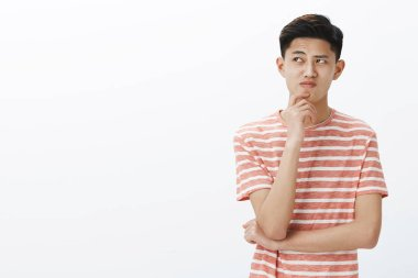 Portrait of troubled young asian guy trying think up plan or idea, standing in thoughtful pose with hand on chin, looking questioned and hesitant at upper left corner, making assumptions