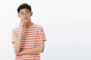 Smart asian guy solving puzzle in mind looking thoughtful and relaxed at upper right corner, thinking, making assumptions touching cheek while making up plan or decision, posing in glasses