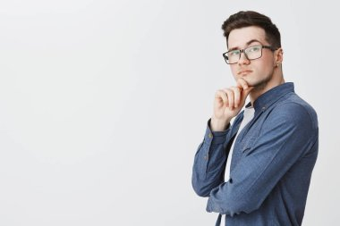 Smart guy in glasses and blue shirt standing in profile turning at camera with thoughtful determined and questioned look holding hand on chin, thinking making assumptions, raising eyebrow curiously