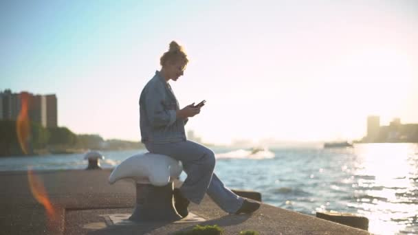 Slow-motion side view of charming young european woman with blond hair in bun sitting in docks turning to sea admiring sunset writing message with smartphone smiling tender at device screen