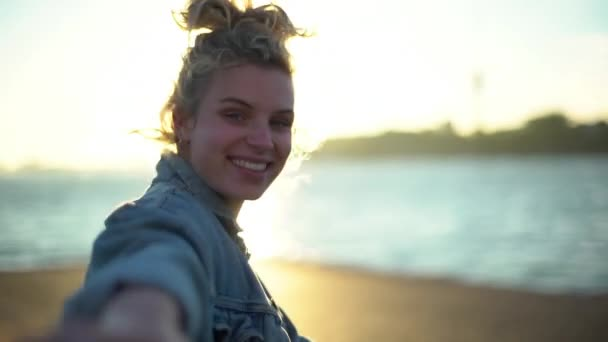 Romantic slow-motion of happy attractive blond girl with blue eyes lead boyfriend to seaside on pier, enjoy sunset, holding hand and turning at camera with cute lovely smile. Follow me concept