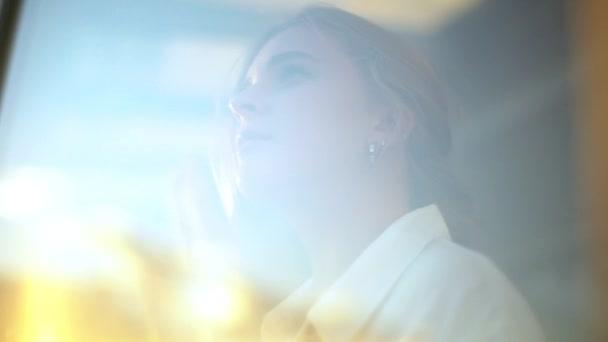 Slow motion sognatore indoeuropeo ragazza attraente guardando attraverso la finestra contemplando cieli blu bello tramonto cercando sole toccante vetro pensiero premuroso avendo alta spera felice futuro