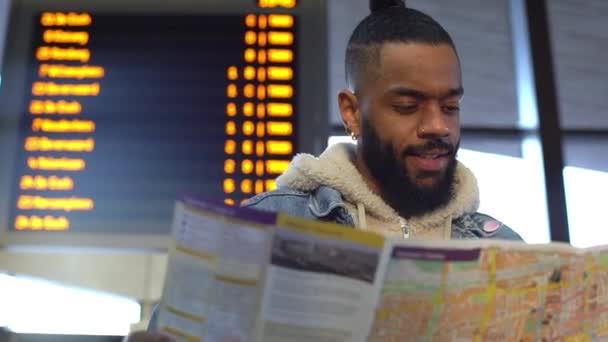 Rallentatore bello afroamericano uomo barbuto che viaggiano, holding mappa, alla ricerca di itinerari, controllo del percorso hotel, leggere il foglio illustrativo di lingua straniera, in piedi contro il bordo di partenza stazione ferroviaria