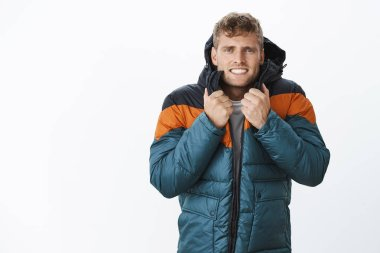 Jeez freezing cold. Portrait of intense trembling handsome european blond man clenching teeth wearing winter puffer jacket suffering from low temperature and bad weather posing over gray background