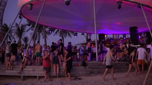 Tourism, summer vacation, travelling concept. Slow-motion evening party sandy beach tropical island festival concert people dancing have fun outdoors near ocean shore relaxing holiday