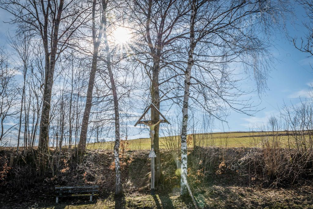 Way cross at a hiking trail in Bavaria with wooden bench and sunshine, Germany