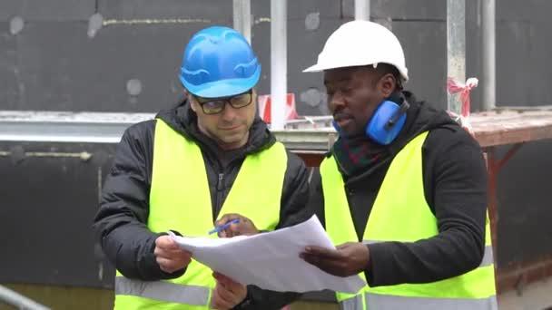 Afrikanischen amerikanischen und kaukasischen Männchen Ingenieure tragen Sicherheitsweste und Helm, die Überprüfung von technischen Zeichnungen und Büro Baupläne unter Gerüst