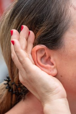 Cropped image of a woman putting her hand to the ear and listening carefully