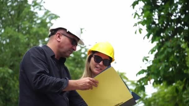 Zwei Bauingenieure, ein Mann und eine Frau, mit Schutzhelmen, die die Baustelle inspizieren und die Projekte überprüfen