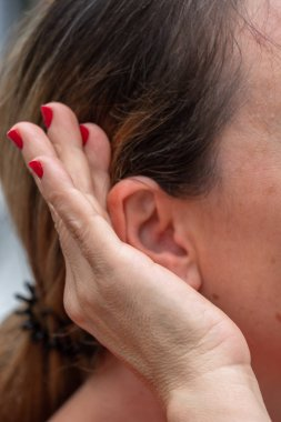 Keeping an eye out. Cropped image of a woman putting her hand to the ear and listening carefully