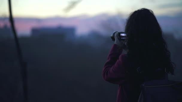 bella fotografa femminile scattare foto del tramonto