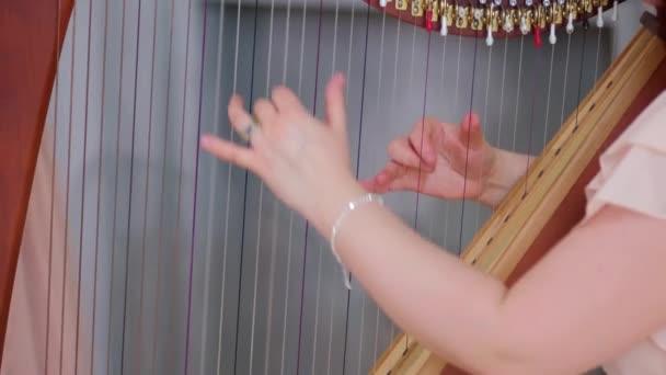 Egy fiatal lány ihletett hárfán játszik. Húrok és kezek