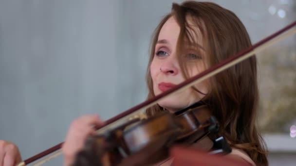 Egy gyönyörű hegedűs hegedül. Közelről.