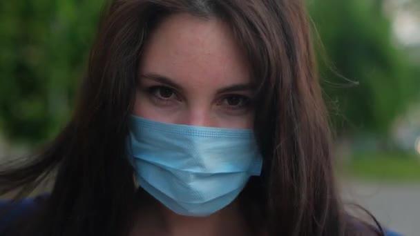 Das Mädchen in der Maske starrt und fixiert ihre Haare. Nahaufnahme, Zeitlupe