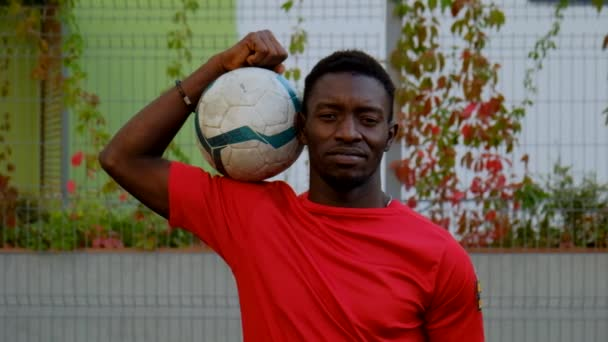 Black guy soccer player stands with a soccer ball on his shoulder
