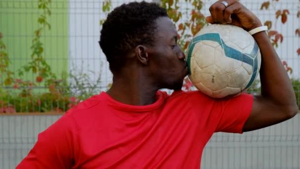 Schwarzer Fußballspieler küsst den Ball und blickt in die Kamera