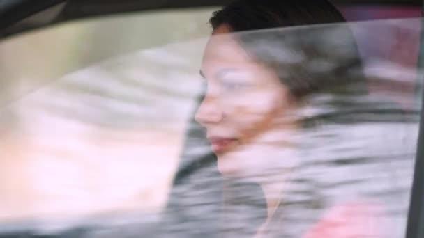 Eine junge schöne Frau in einem roten Kleid in einem roten Auto rollt das Fenster herunter und lächelt. Fahrerin auf der Straße