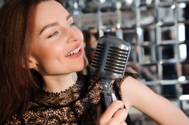Rock star. Sexy Girl singing in retro microphone