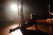 Mladá sexy žena vykonávat pól tanec na tmavém pozadí.
